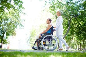 30225563 - pretty nurse walking with male patient in a wheelchair in park